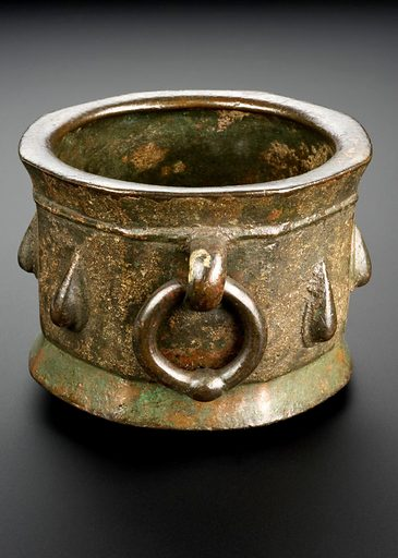Bronze mortar, Iran, 1301–1400. A mortar is a bowl used with a pestle to crush and grind ingredients for drug preparations. Drugs were often in the form of powders, ointments or solutions. This octagonal mortar is made from bronze and has a loop handle. It is quite heavy, weighing just over 4 kg, so it would not have been knocked over easily. See how it is unbalanced at the base? The foot of the mortar has worn because of use and there is also a crack in one side where over time the pounding of the pestle has damaged the bronze. This mortar was made in Persia (modern day Iran). Contributors: Science Museum, London. Work ID: mcybr423.