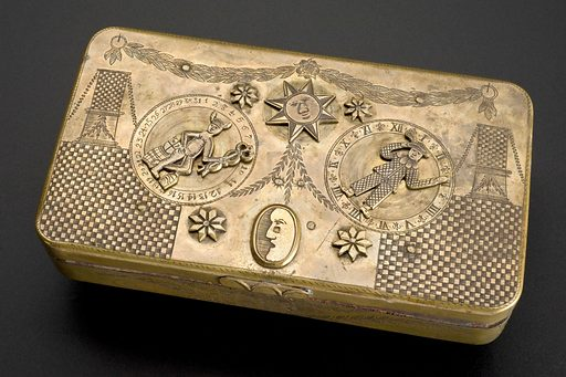 Brass tobacco box, Europe, 1801–1880. To open this brass tobacco box, one had to solve the puzzle of the locks. Perhaps the owner was concerned some might get stolen if he wasn't careful. Ironically, given the health problems that would later be associated with tobacco, the front is engraved with the figure of Asklepios, the Greek and Roman god of healing and medicine, and his symbol, a snake entwined around a rod. Tobacco boxes were very personal items and came in a variety of shapes, sizes and decorations. Contributors: Science Museum, London. Work ID: v2cwgm4n.