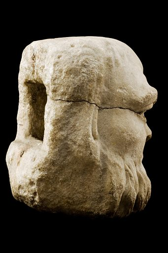 Limestone fountain spout in the form of grotesque head, Roman from Spain, 100 BC to 400 AD. 3/4 view, from behind. Black background. Contributors: Science Museum, London. Work ID: amuwtsbj.