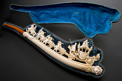 Carved meerschaum cigar holder (large), representing the coronation of King Ludwig II of Bavaria, carved coach, seven horses, livery amber mouthpiece, in leatherette case, A Zimmermann (supplier), Munich, Bavaria, Germany, 1864–1867. Pipe photographed in its case. Graduated matt black perspex background. Contributors: Science Museum, London. Work ID: kfg3qknv.
