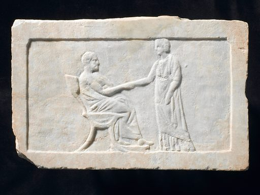 Marble relief marking a grave, Greece, 350–300 BCE. Like many other graves of the time, this marble relief shows a scene of parting and farewell. Here a woman is clasping the hand of an old man. Contributors: Science Museum, London. Work ID: xfuam4vz.