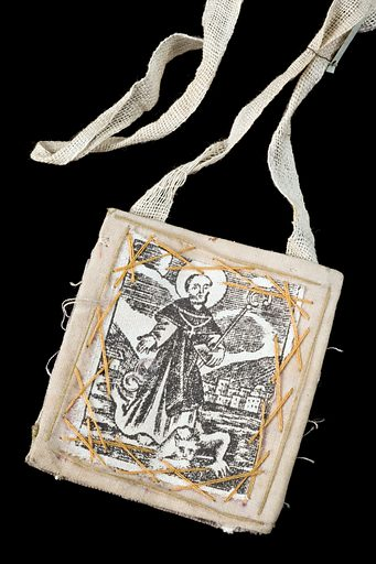 Cloth amulet, Spain, 1800–1920. This simple cloth amulet was worn around the neck and was said to protect the wearer from toothache, snake bites and rabies. The figure stitched into the cloth is a saint who believers would call on for protection against disease and cures for illness. Contributors: Science Museum, London. Work ID: nmrdstqk.
