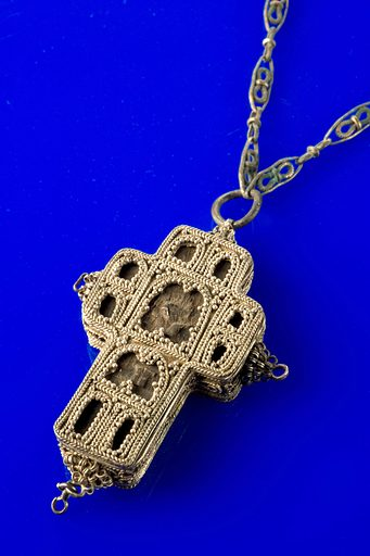 Amulet, carved cross of yew wood with representations of Christ, encased in elaborately decorated silver cross and suspended from ornate chain, from Pec, Yugoslavia, 1801–1900. Full view of cross, blue perspex background. Contributors: Science Museum, London. Work ID: nmu654hc.