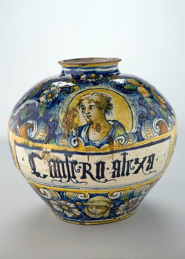 """Drug jar for Conserve of Alexandrian Roses, Venice, Italy, 1 The inscription painted on this earthenware jar is a shortened form of the Latin phrase Conserva di Rose Alessandrino, which translates as """"Conserve of Alexandrian Roses"""". The petals of these roses would have first been pounded in a mortar along with sugar. Once a jam-like product had been formed, the treatment would be taken orally, acting as a strong laxative. The vase is decorated with the figure of a soldier in Italian armour and dress. Contributors: Science Museum, London. Work ID: brkfg3tu."""