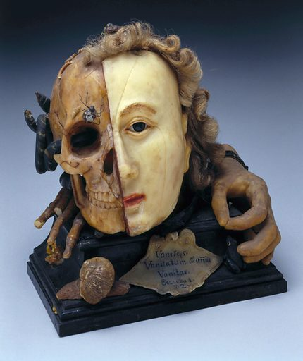 """Wax vanitas, Europe, 1701–1800. Vanitas are works of art intended to remind the viewer of the shortness of human life, the uselessness of vanity and the certainty of death. This example features many symbols typical for this type of object, such as a skull and insects that feast on decaying flesh. The other side of the model shows the face during life. The verse scratched on to the front is from the biblical book of Ecclesiastes and reads """"vanity of vanities, all is vanity"""". Contributors: Science Museum, London. Work ID: acux9qcx."""