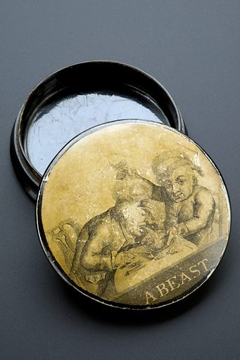 Snuff box, England, 1771–1830. Two gentlemen are pictured sitting at a table surrounded by tobacco and smoking pipes. One is comforting the other who is being sick after too much smoking. The illustration is titled 'A Beast', probably referring to the effects shown in the picture. The papier mâché box was used to store snuff, tobacco that is snorted or inhaled through the nose. Snuff, a powdered form of tobacco, was popular in the 1700s and 1800s for its stimulating nicotine boost and was also believed to help relieve common colds and stop snoring. Contributors: Science Museum, London. Work ID: sybwrc94.