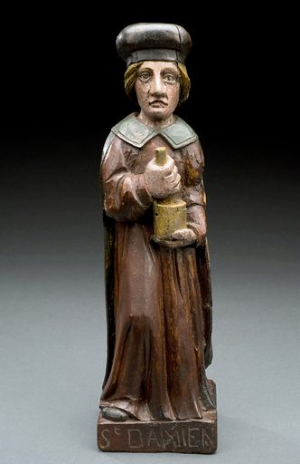 Wooden statue of St Damian, France, 1801–1900. St Damian and his twin brother St Cosmas were physicians who provided medical treatment free of charge in the hope of converting their patients to Christianity. The twins are said to have died for their Christian beliefs in the 300s CE. Saint. Mortar. Pestle. Contributors: Science Museum, London. Work ID: ps2re82m.