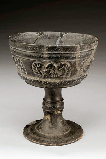 Large handle-less kantharos, Etruria (Italy), 600–550 BCE. A kantharos is a cup used for drinking wine and water. It normally has handles, unlike this one. The cup is decorated with winged male heads which are usually associated with the Greek god Hermes. Hermes was the messenger of the gods, led the dead to the underworld and was worshiped as a god of fertility. This chalice is from Etruria, an ancient state of Italy, now part of Umbria and Tuscany. The colour and design is typical of Etruscan pottery and would have been polished to give a high shine. Contributors: Science Museum, London. Work ID: fs3kjxs8.