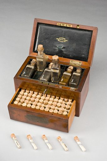"""Homeopathic medicine chest, Northamptonshire, England, 1801–. This mahogany medicine chest contains 69 small glass vials with handwritten labels and six large bottles. Homeopathy relies on the idea that 'like cures like'. For instance, if you are vomiting, your treatment will be something that causes vomiting but in a smaller, much diluted dose. One of the large bottles is labelled """"Urtica urens"""". This treatment is made from a dwarf stinging nettle and is used on burns and skin irritations, the same effect the plant has on the body. Contributors: Science Museum, London. Work ID: nytbdr94."""