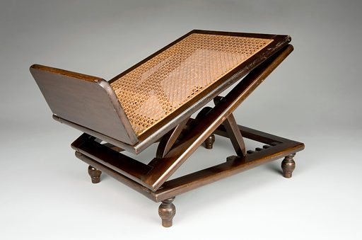Adjustable wooden footrest, England, 1830–1930. Used to rest and raise the foot, this footrest allowed the body time to heal and to avoid further injury. Raising the foot helps to reduce swelling and ease the pain in conditions such as gout. The footrest could also be adjusted to different heights using a ratchet, a similar system to a deckchair. There is also a wooden bar to rest the foot in an upright position. This object is made from the hard wood mahogany and could have been used both in hospitals and at home. Orthopaedics. Contributors: Science Museum, London. Work ID: wzxczwuq.