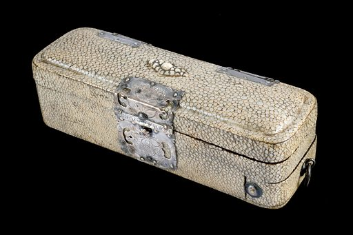 """Surgical instrument set, Europe, 1650–1685. This instrument case contains a scalpel and curettes, which were instruments used for scraping and cleaning a diseased surface. It is covered with shagreen (stained fish skin) with silver decorations. The handwritten inscription in one of the drawers reads """"Dr Shumatt surgical case came from France in the time of the Revolution – The abolition of the Edict of Nantes 1685"""". The Edict of Nantes, 1598, gave some religious freedoms to French Protestants, known as Huguenots, who previously had been persecuted. Many Huguenots left France and brought their skills to other countries in Europe. Contributors: Science Museum, London. Work ID: vvazgvk6."""