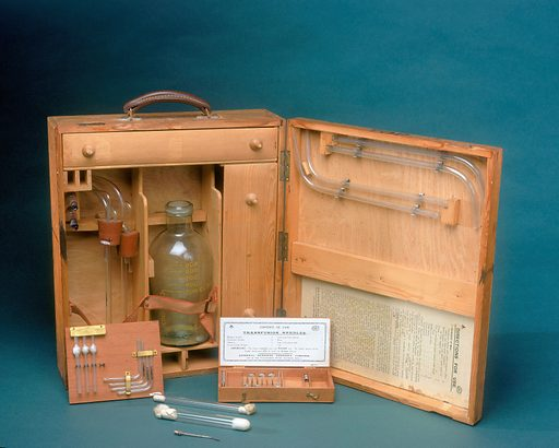 Blood transfusion apparatus, United Kingdom, 1914–1918. It's 1917, and you are a wounded soldier at a casualty clearing station on the Western Front. You are bleeding badly and going into shock. You are in danger of dying and urgently need blood – where's the nearest blood bank? He's right next to you. Your blood transfusion will come directly from another patient. Is it safe? It's the best method available at the time, particularly if your surgeon is Lieutenant Geoffrey Keynes of the Royal Army Medical Corps. He designed and pioneered this portable blood transfusion kit, with a special device in the flask for regulating flow. Why didn't Keynes use stored blood? It didn't keep very well. It needed to be refrigerated – a difficult task in field hospitals, and it clotted into lumps unless an anticoagulant was added. While it became technically possible to do this during the First World War, the patient-to-patient method was still more widely used. Matching of blood groups was recommended, but there was not always time. The first blood banks stored O type blood – suitable for all recipients. But in the meantime, you were lucky to have reached a casualty clearing station, to take your chances with an emergency transfusion. And who better than with Lieutenant (later Sir) Geoffrey Keynes? In 1921 he co-founded London's Blood Transfusion Service, and a year later published Britain's first textbook on the subject. Contributors: Science Museum, London. Work ID: gmz8tngz.