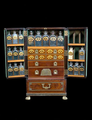 Medicine chest, winged front, from Reece's Medical Hall, Piccadilly, with 30 painted glass bottles and 4 drawers, 5 confection glasses, 1 probang, 3 boxes, 1 plaster spreader, 1 seal, 1 spatula, 1 bowl, 1 pill tile, 1 fleam, 1 lancet, 2 syringes, 4 visiting cards, 1 receipt and engraved plate, c1805. Chest open, shot on black background. Contributors: Science Museum, London. Work ID: pjeqhgug.