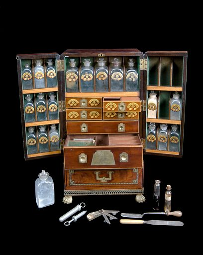 Medicine chest, winged front, from Reece's Medical Hall, Piccadilly, with 30 painted glass bottles and 4 drawers, 5 confection glasses, 1 probang, 3 boxes, 1 plaster spreader, 1 seal, 1 spatula, 1 bowl, 1 pill tile, 1 fleam, 1 lancet, 2 syringes, 4 visiting cards, 1 receipt and engraved plate, c1805. Chest open showing compartments and instrunments. Black background. Contributors: Science Museum, London. Work ID: xwxhxney.