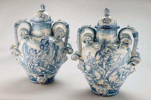 Pharmacy vase, Italy, 1740. The devil's head at the base appears to be a dispensing hole for the contents of the large jar on the left (measuring 480 mm in height). Entwined snakes form the handles. The blue and white decorations show scenes of Roman battle and a Roman soldier dying from an arrow wound. The other side depicts more pleasant scenes of gods feeding each other grapes and a girl walking with a dog in the countryside. It is shown with a similar example (A631894). Drug jar. Contributors: Science Museum, London. Work ID: gcjmpmvx.