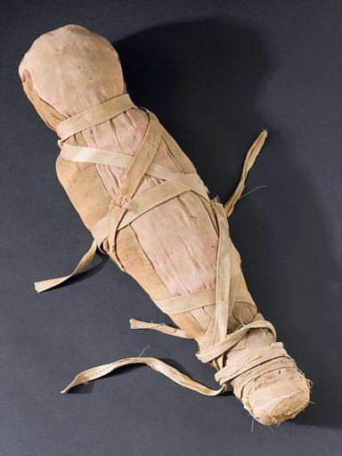 Mummified infant, no provenance, Egypt, 2000 – 101 BC. Top three quarter view. Black background. Contributors: Science Museum, London. Work ID: jqs39cf8.