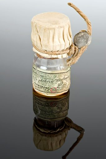 """Bottle of Behring's diphtheria remedy, Germany, 1914–1918. This is a bottle of diphtheria antitoxin developed by Emil Adolf Behring (1854–1917) in 1891. He refined this treatment again in 1913. This bottle of """"Behring's diphtheria remedy"""" was taken from a German battleship during the First World War, the first major conflict where more troops died from their wounds rather than disease. This was partly due to vaccination. Contributors: Science Museum, London. Work ID: h3t5h7nv."""