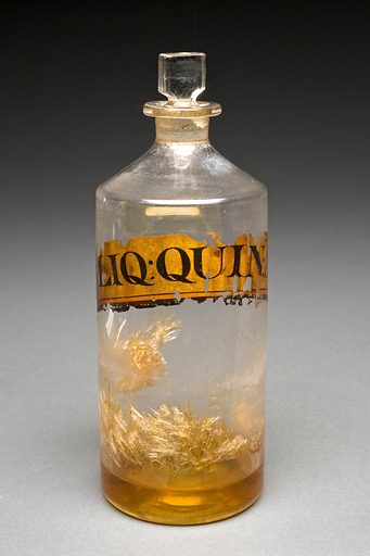 Clear glass shop round for Quinine, England, 1801–1850. This glass bottle was once on the shelves of the prominant English chemists Savory & Moore (active 1794–1992), who were based in London. The label shows that the amber liquid in the bottom is quinine. Quinine is used for pain relief and to prevent fevers and for a long time was the primary treatment for malaria. Contributors: Science Museum, London. Work ID: w3akggwz.