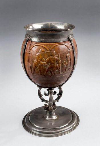 Coconut goblet mounted in silver, York, England, 1671–1700. These carvings show three scenes in the life of a barber-surgeon. One shows a bloodletting scene, a common treatment for a number of illnesses and diseases. The other scenes show a customer waiting for a haircut and shave and a patient with a bandage on his head and who is also waiting to be seen. The coconut would have been a novelty as these were new to England in the 1600s. Contributors: Science Museum, London. Work ID: kb6avr5t.