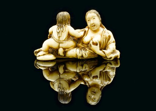 Ivory netsuke showing a mother breastfeeding a child, Japan, 1701–1900. Netsuke are toggle-like ornaments. They hang objects such as medicine boxes or tobacco pouches from the sash of the kimono, the traditional form of Japanese dress. This example is carved from ivory and shows a mother breastfeeding a child. Contributors: Science Museum, London. Work ID: rbzemqqr.