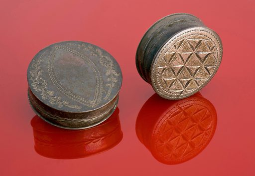 Silver pill box engraved with a triangular pattern, Birmingh. Boxes like these could be used to store pills, cachous (breath fresheners made from cashew nuts and liquorice), and maybe even patches – such as the small black felt or silk shapes to cover blemishes on the skin, which were often the result of smallpox. Contributors: Science Museum, London. Work ID: j6tnvmt4.