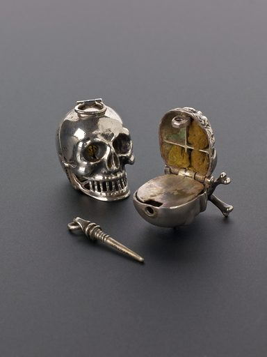 Silver vinaigrette in the shape of a skull, Europe, 1701–180. Likes pomanders, vinaigrettes could be used as a vessel to hold strong smelling substances to be sniffed should the user be passing through a particularly smelly area. At a time when miasma theories of disease – the idea that disease was carried by foul air – were dominant, carrying a vinaigrette was considered a protective measure. Vapours from a vinegar-soaked sponge in the bottom were inhaled through the small holes in the top of the 'acorn'. If a person felt faint they could also sniff their vinaigrette and the sharp vinegar smell might shock the body into action. The skull was probably hung from a piece of cord or necklace and carried at all times. It is shown here with another skull-shaped example (A641486). Contributors: Science Museum, London. Work ID: apbjjwcq.