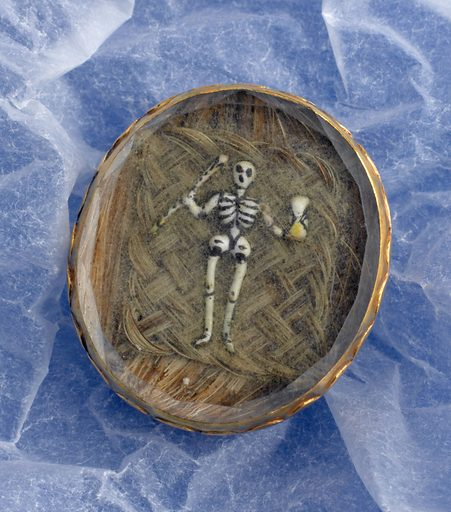 Memento mori, Europe, 1689. Jewellery like this brooch containing human hair is associated with mourning. The hair is almost certainly from a departed loved one. Objects such as these were called memento mori, or 'reminder of death'. The skeleton holding an hourglass reminded the wearer of the shortness of their life. The brooch has two loops on the back to attach it to a belt or to put in the hair. It is engraved with the initials of the person who died, 'W H', and the date 1689. Contributors: Science Museum, London. Work ID: ds5vdemp.