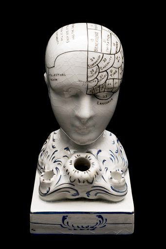 Earthenware phrenological bust, also designed as a penholder, with areas marked off in underglaze black, by F Bridges, England. Full frontal view, black background. Contributors: Science Museum, London. Work ID: v9dwjxtm.