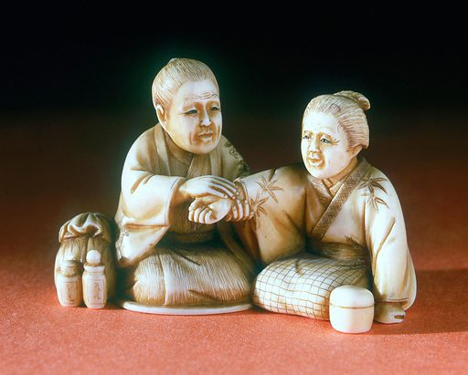 Ivory netsuke, Japan, 1871–1900. A doctor is feeling the pulse of his female patient in this small ivory netsuke. Netsuke are toggle-like ornaments used to hang objects, such as medicine boxes or tobacco pouches, from the sash of a kimono – a traditional form of Japanese dress. Traditional Chinese Medicine. Contributors: Science Museum, London. Work ID: fj5pc6v2.