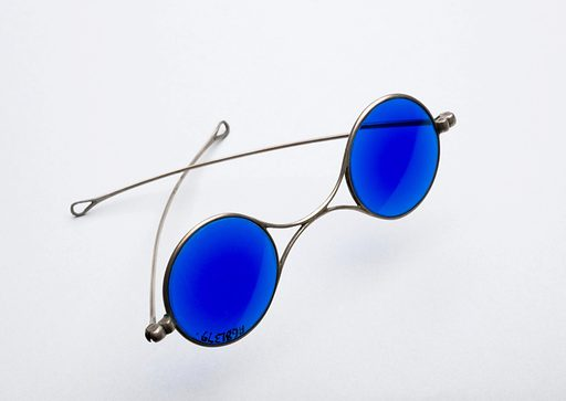 Sunglasses with dark blue lenses, England, 1860–1900. Blue tinted lenses indicate these spectacles were for outdoor use. They protected from bright sunlight. They are a Victorian version of the sunglasses we wear today. The frames are made from silver. Prescription lenses help correct vision. Protective spectacles – sunglasses. Contributors: Science Museum, London. Work ID: zrvr9ry8.