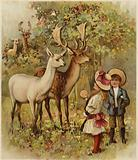 Two young children feeding the deer in a park