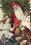 Girl being shown illustrated book by Father Christmas
