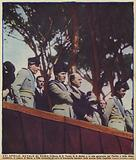 Italian Fascist Party leaders Benito Mussolini, Augusto Turati, and Giuseppe Bottai listening to a choir of 30,000 …