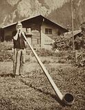 Man blowing an alphorn in the Alps
