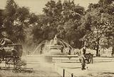 Workmen spraying tar on the gravel in front of a fountain beside Park Lane
