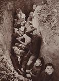 Hop pickers in Kent, many of them children, taking cover in a trench as aircraft battle in the skies above them, World War II, 1940