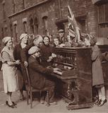 People enjoying a tune on a piano saved from a bombed house during the Blitz, World War II