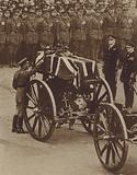 King George V placing a wreath on the coffin of the Unknown Warrior resting on the gun carriage taking it from the Cenotaph to Westminster Abbey, Armistice Day, 1920