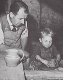 Potter teaching his two year-old son to use the potter's wheel