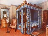 A Hepplewhite Bedroom. Chintz-Curtained Inlaid Satinwood Bed. Inlaid Satinwood Dressing Chest and Mahogany Wardrobe.