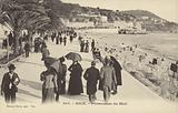 People taking a lunchtime walk along the promenade on the beach front in Nice