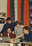 Textile designers of the state-owned Tientsin dyeing and printing plant draw inspiration from various examples of folk art, People's Republic of China, 1950s