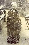Boy standing, covered in strings of conkers