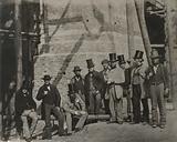 Group of men posing beside a bridge under construction or repair, 19th Century