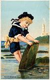Boy looking under stone on beach
