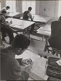 Four men sketch at drafting tables