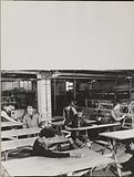 A group of men inspects wooden tables