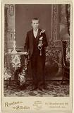 Unidentified young man standing, holding book and beads