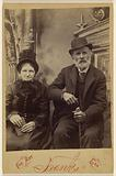 Unidentified old woman and bearded old man, seated, both wearing hats