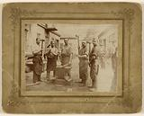 Five blacksmiths near an anvil, each holding a large hammer